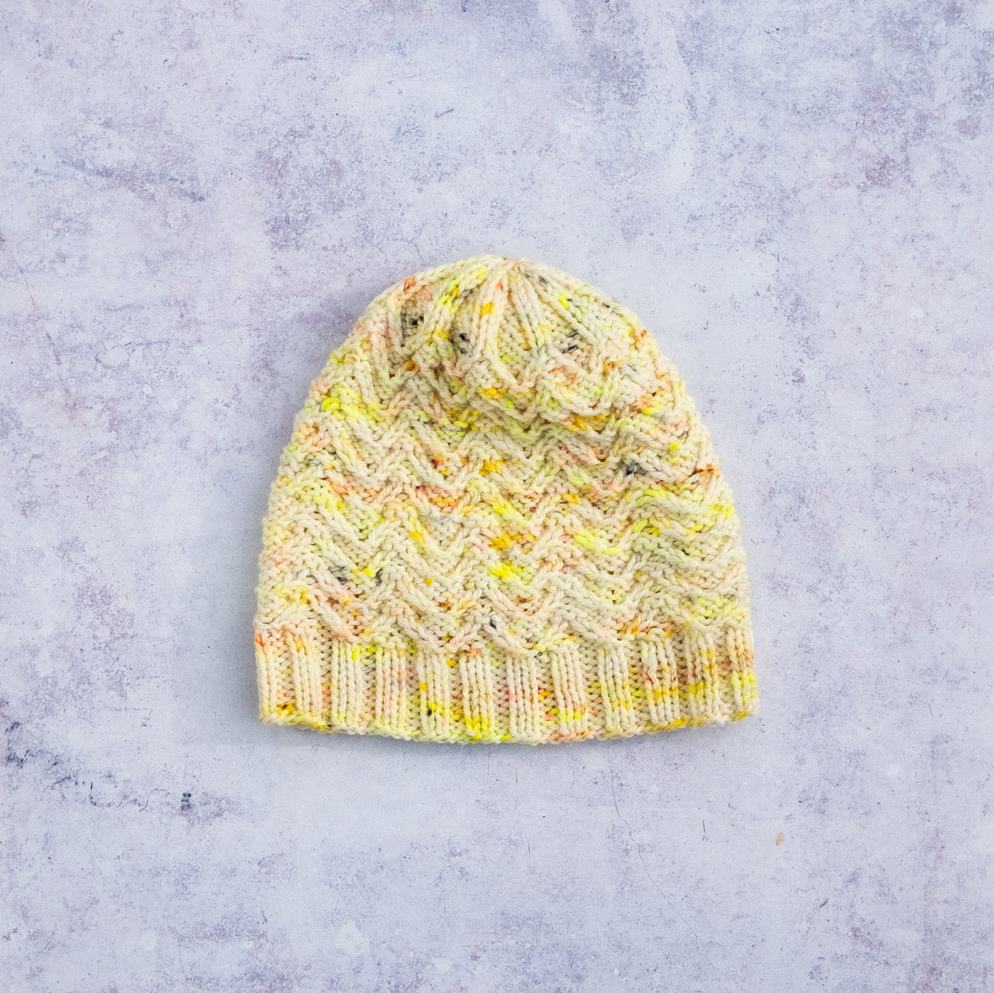 Handknit hat laying flat, it has textured stitches in white yarn speckled with neon yellow, gold and flecks of coral here and there. The crown of the hat has in interesting decreasing pattern, the texture of the stitches come together a little like a flower motif.