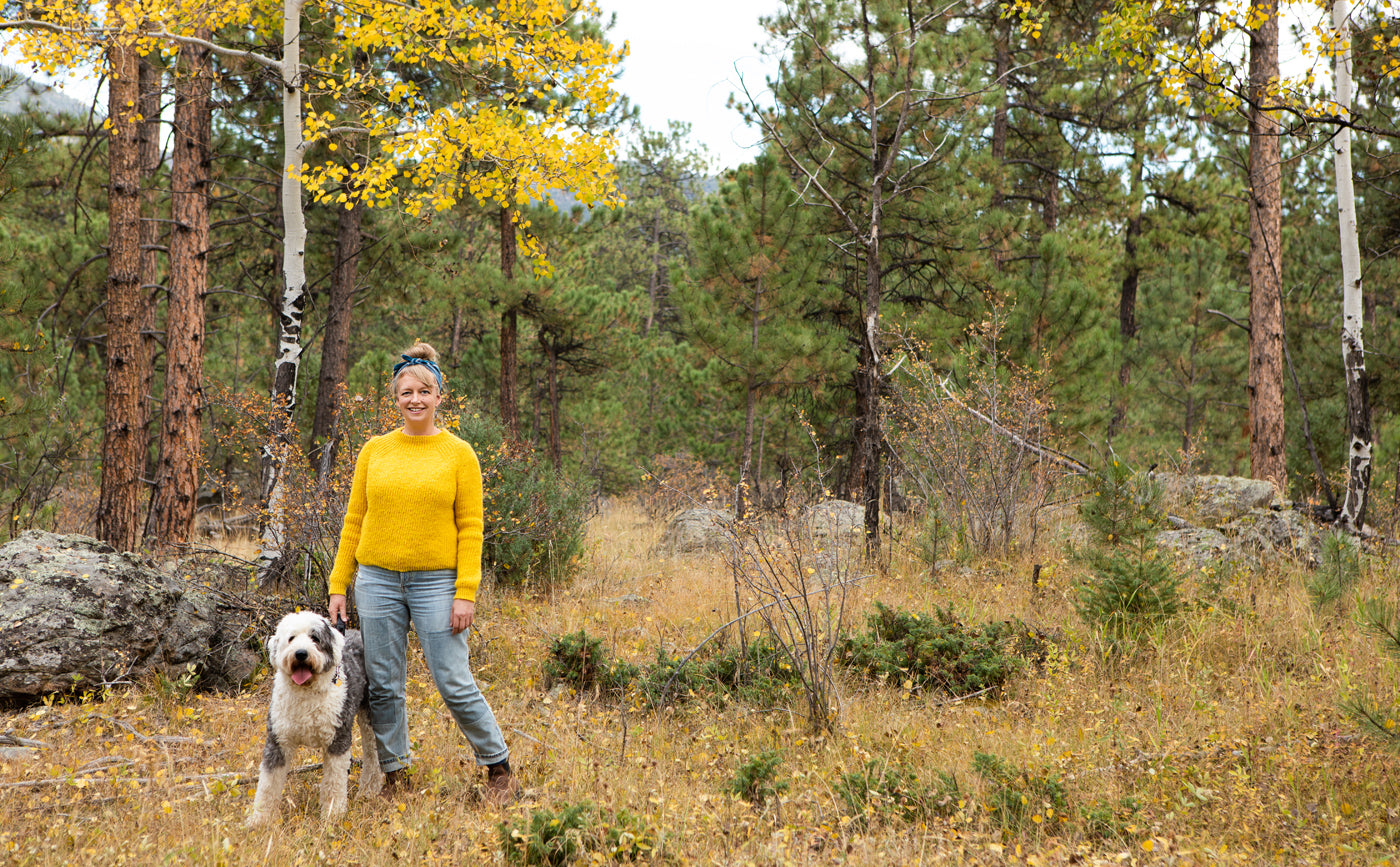 This is an image of Amber wearing a yellow sweater standing in a yellow Aspen grove with her dog Beatrix, a English Sheepdog