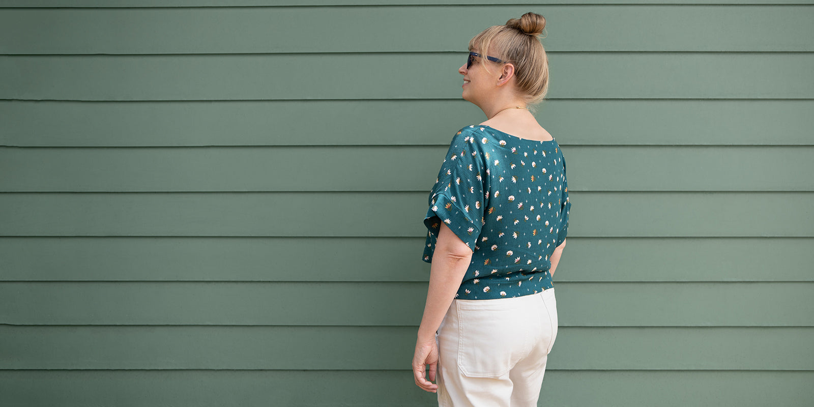 This is an image of a woman wearing a green floral top and white pants standing in front of a green wall.