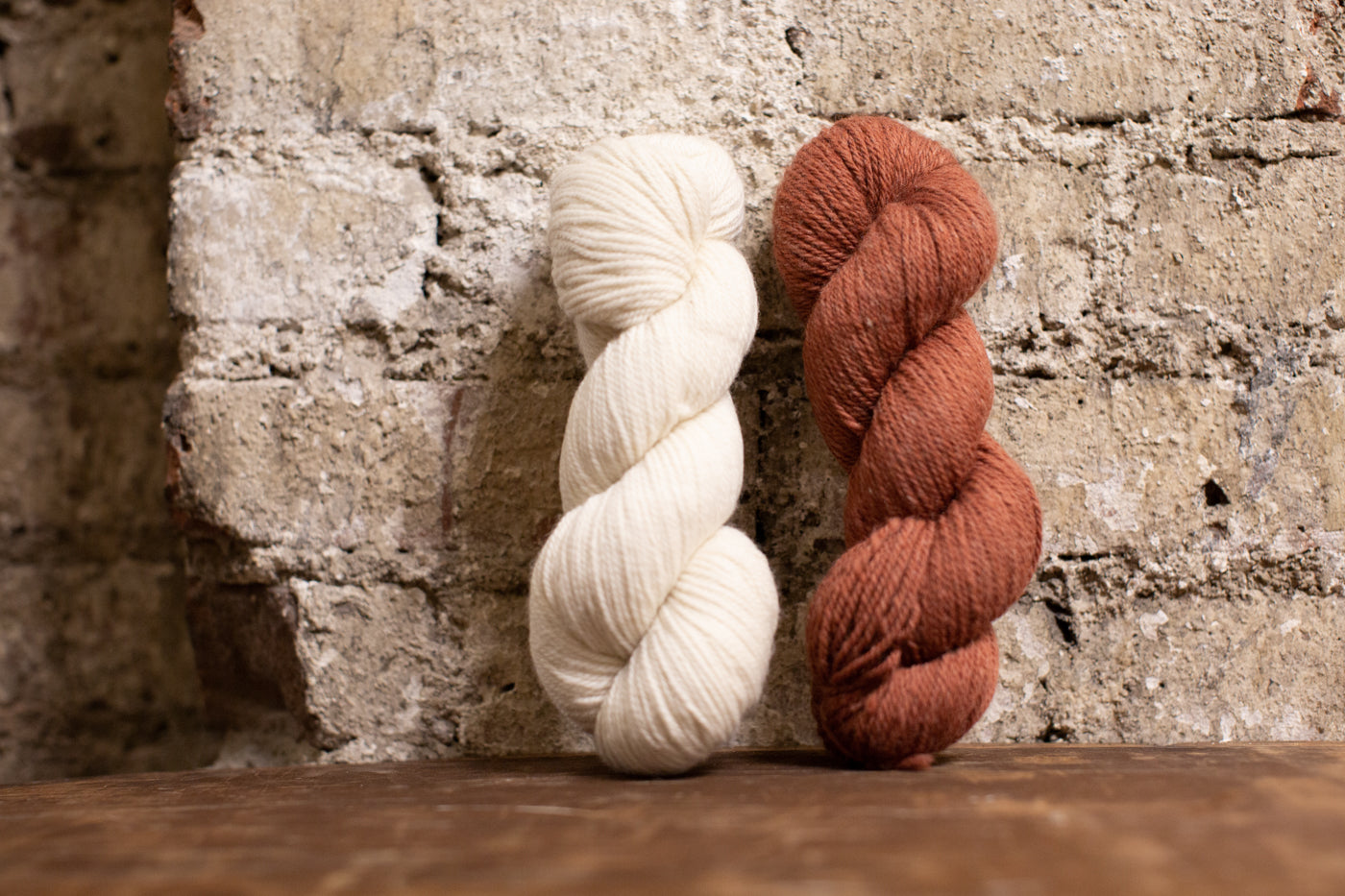 White yarn and muted red yarn leaning against a white wash brick wall.