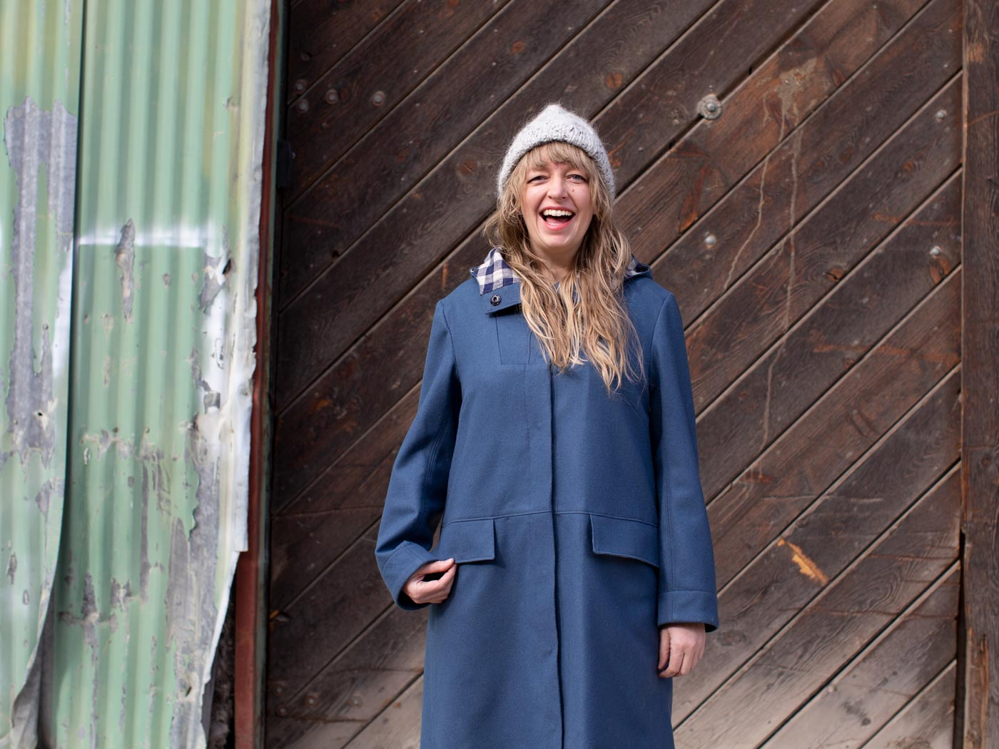 A person with long blonde hair stands smiling in front of a large barn-wood door. They wear a blue wool parka, a woolly beanie, and with one hand tugs at the pocket of their coat.