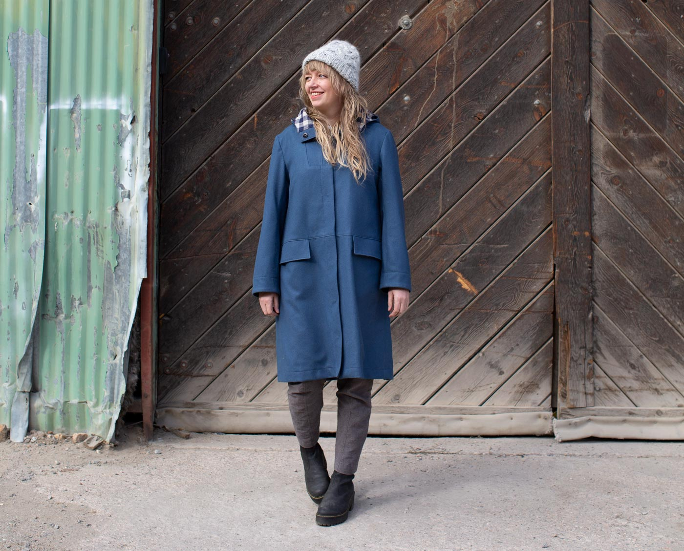 Amber stands smiling in her uniform-blue, melton wool parka in front of a green corrugated building with large barn wood doors.
