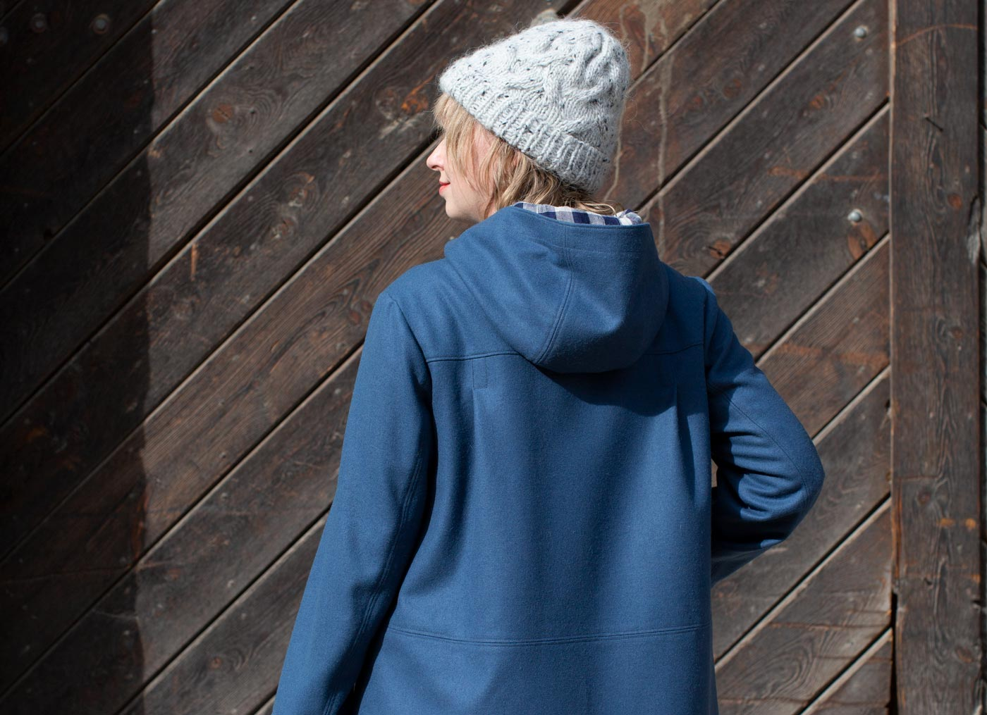 Amber stands facing away, showing the back of the uniform-blue parka. There are pleats on each side of the coat at her shoulder blades, and her hood is down, resting on the back of the coat.