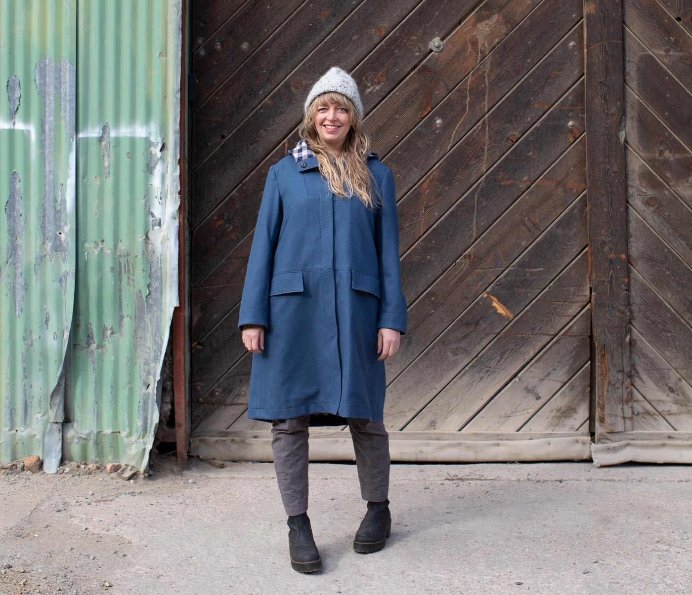 Amber stands in her blue wool parka smiling.