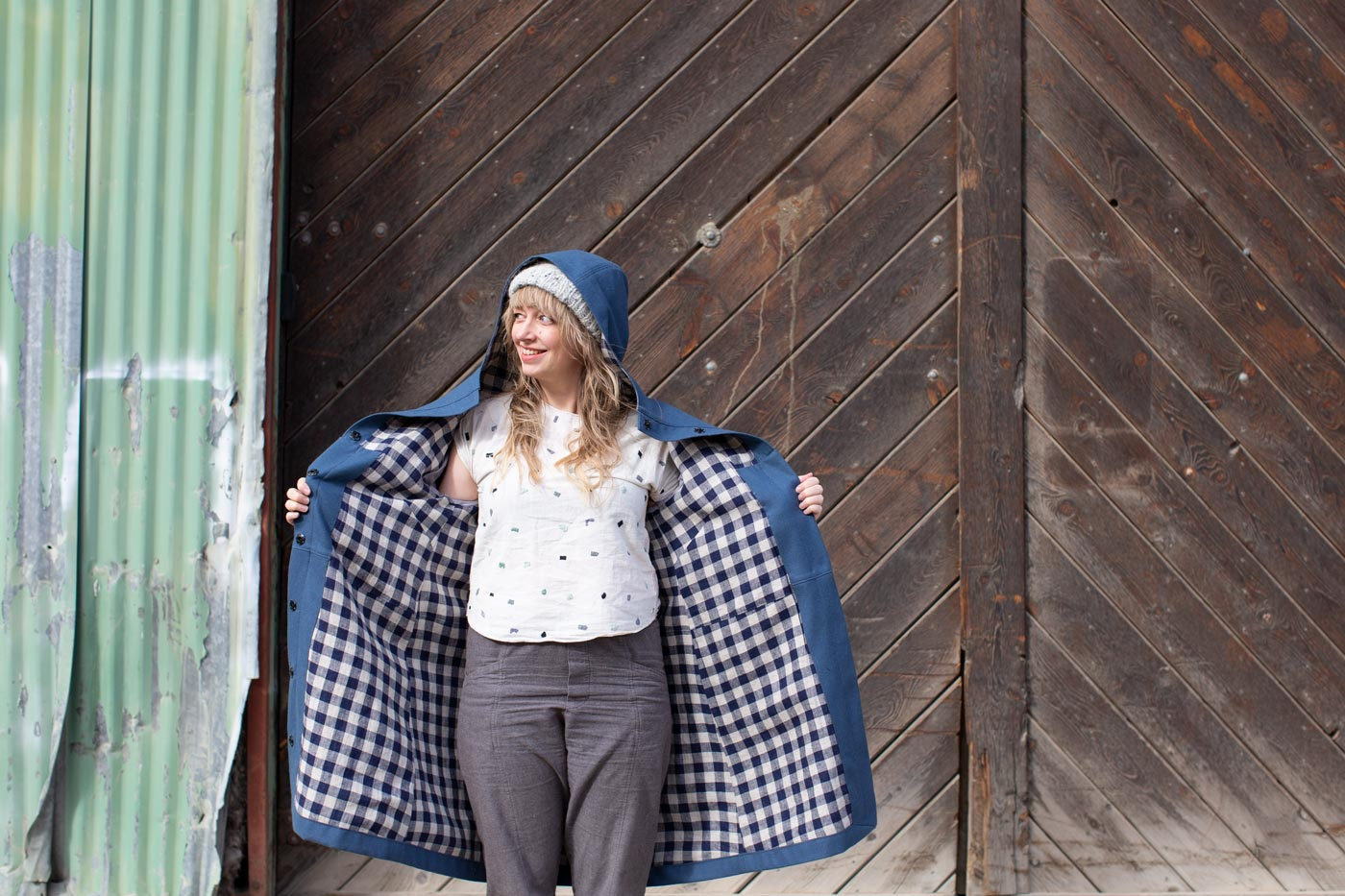 Amber holds her blue wool parka open, showing off a silver and navy linen gingham lining.