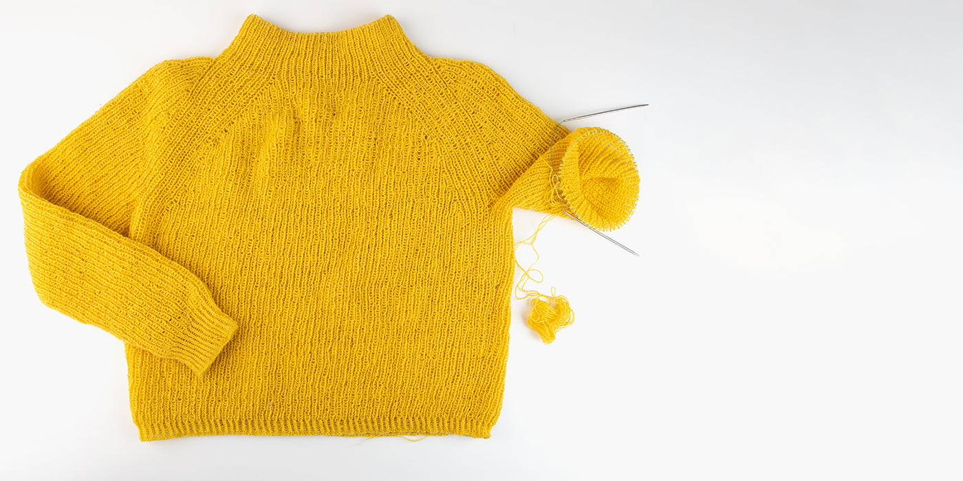 yellow sweater being knit with yarn and knitting needles