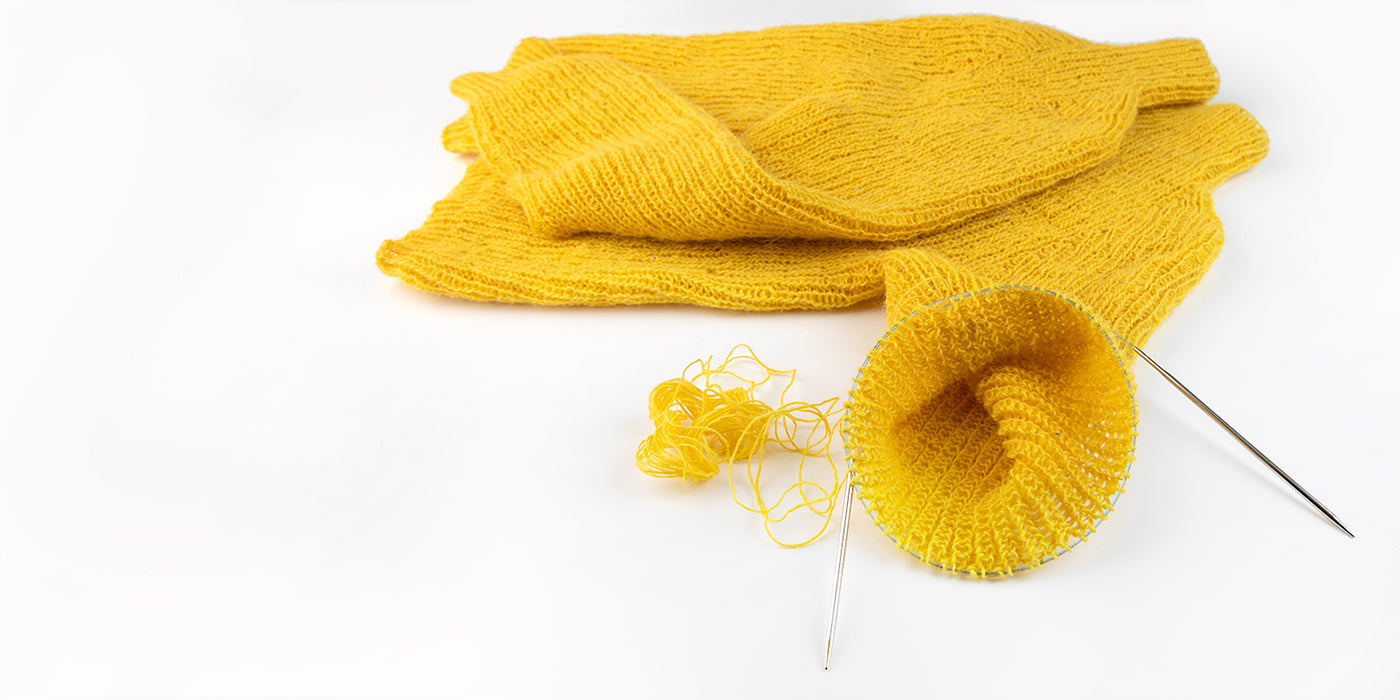 closer view of an incomplete sweater from the armhole that is being knit with circular needles