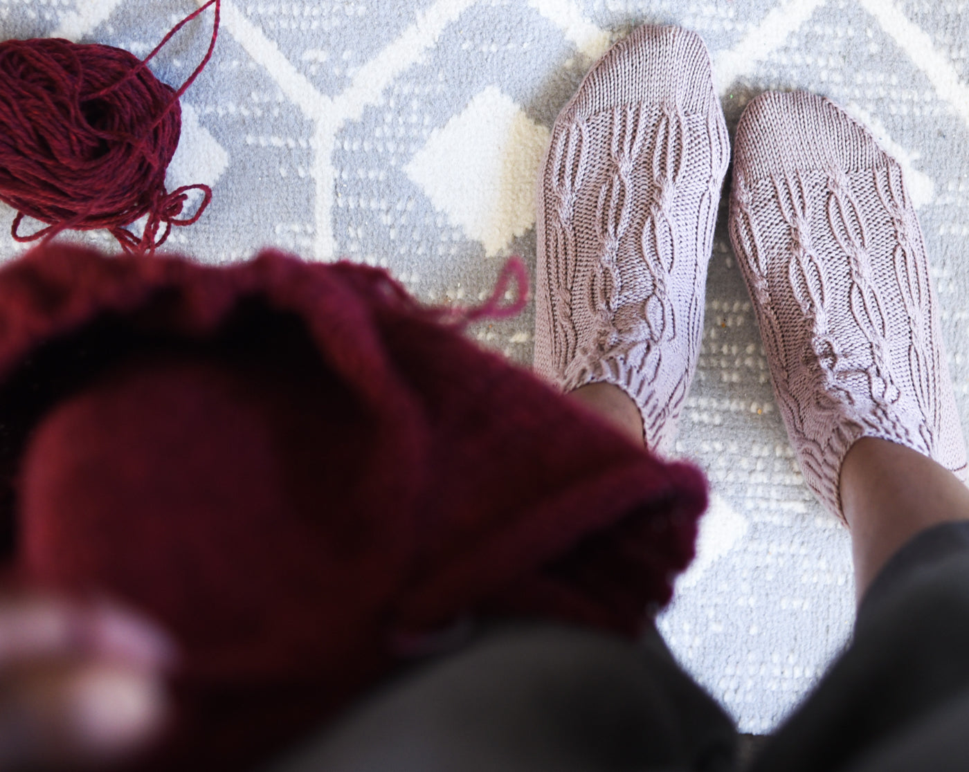 Photograph of looking down at feet showing the cable knitting of the socks.  The background is a blue and white patterned rug.