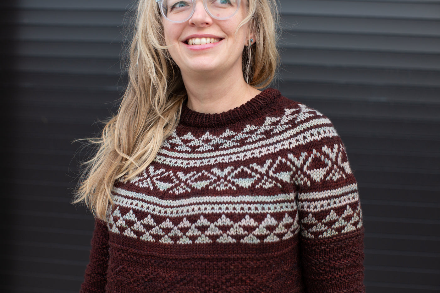 A women wearing a burgundy sweater with mint green accents.  The photograph is up close to show the pattern of the knitting.  The photograph is cropped from the women's forehead to elbows.