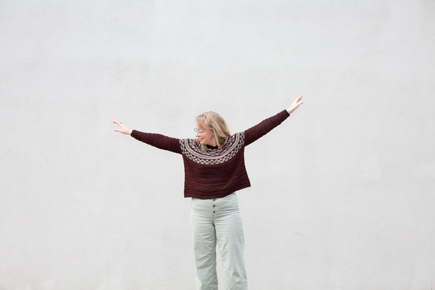 Amber standing in front of a white wall with her arms out, showing her new knitted sweater.  The sweater colors are burgundy and mint, Amber is wearing light green pants.