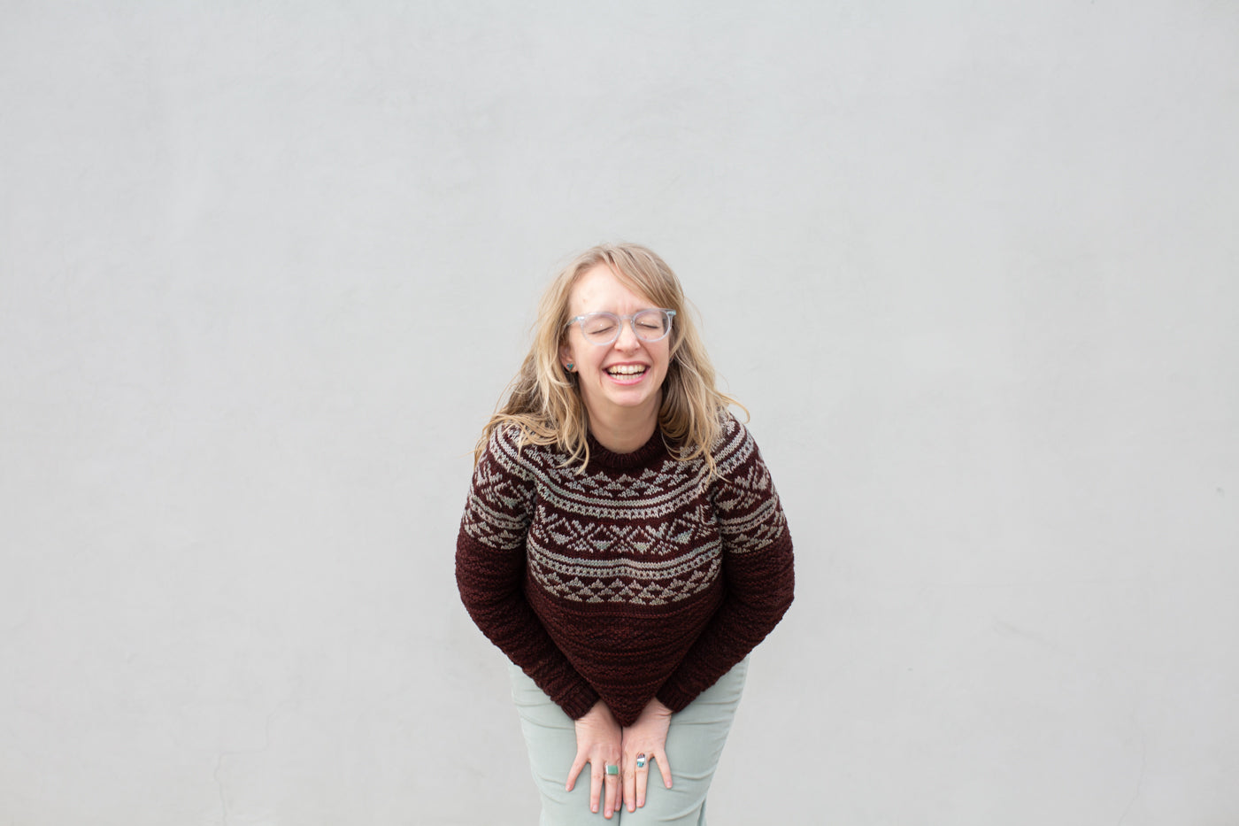 Amber doubled over laughing in front of a white wall wearing a burgundy/mint knitted sweater and light green pants.
