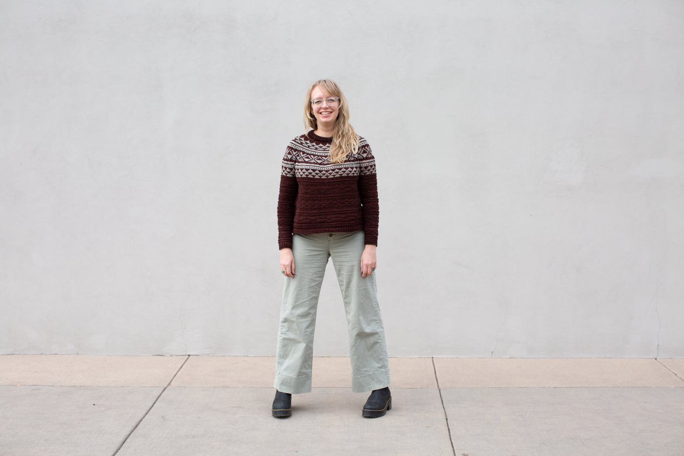 Amber standing in front of a white wall on a city street with her hands to her side, facing the camera and smiling.  Amber is wearing a burgundy/mint green knitted sweater with light green pants.