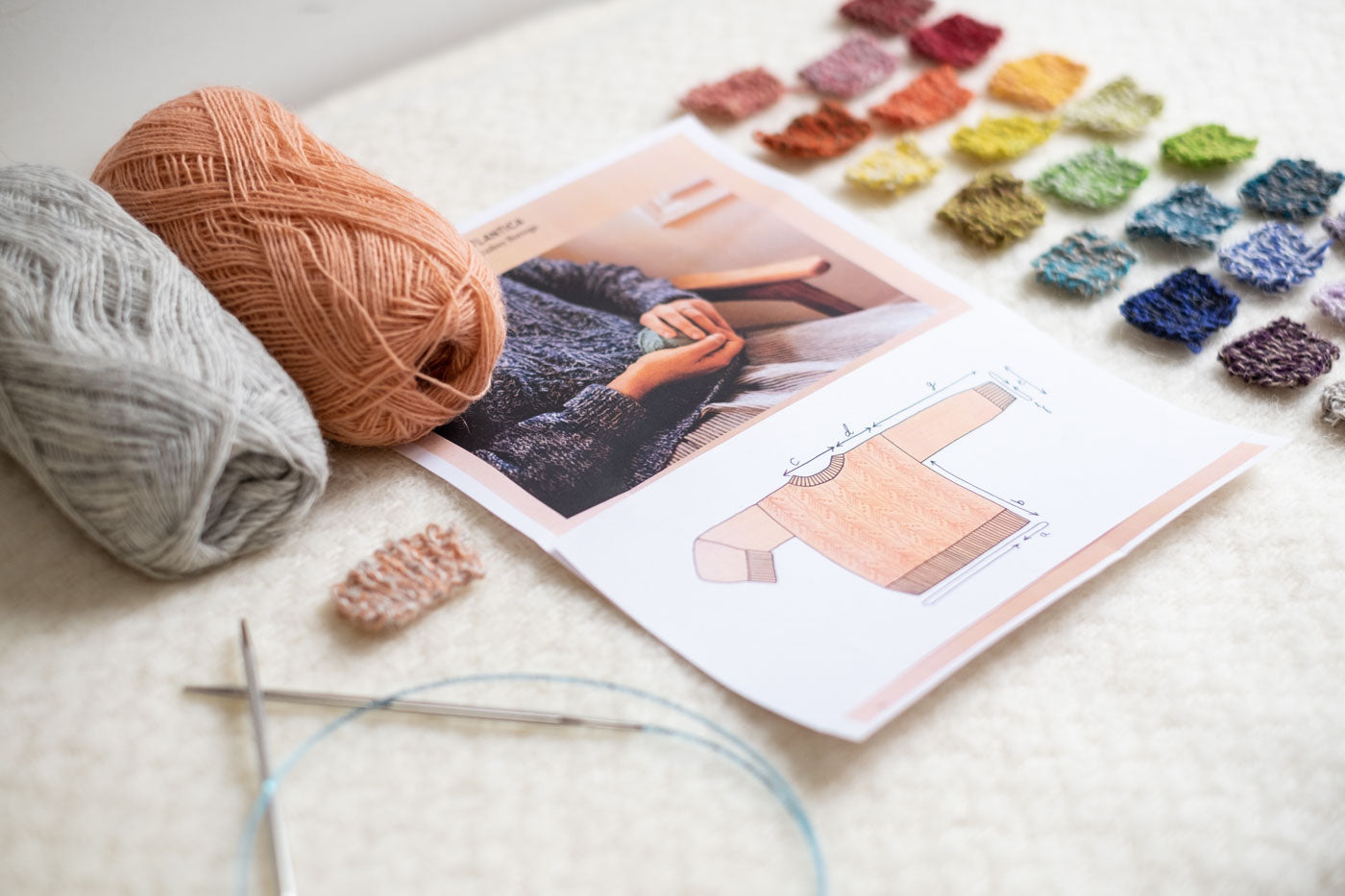 Two balls of yarn in gray and pale peach are displayed next to a pattern featuring a cable-knit sweater along with dozens of small knit swatches and knitting needles.