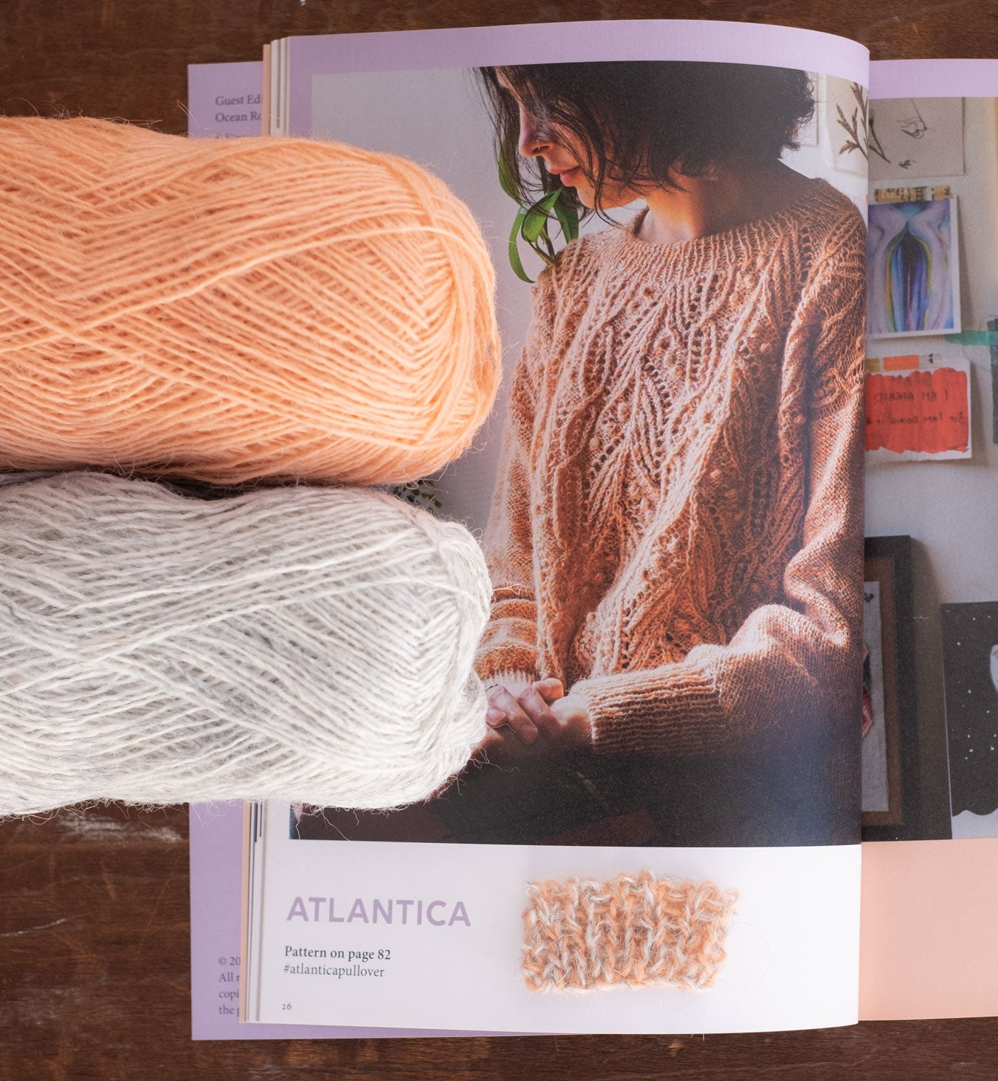 A magazine lays open to a page showing a person with chin-length curly hair wearing the Atlantica Pullover—a delicate lace and cable sweater with a slightly oversized fit. It is a pale, muted peachy color. Two balls of laceweight yarn are on top of the magazine, peeking into the frame of the picture. One is pale heathered grey and one is a warm pale peach. They are held together to created the muted marl fabric.