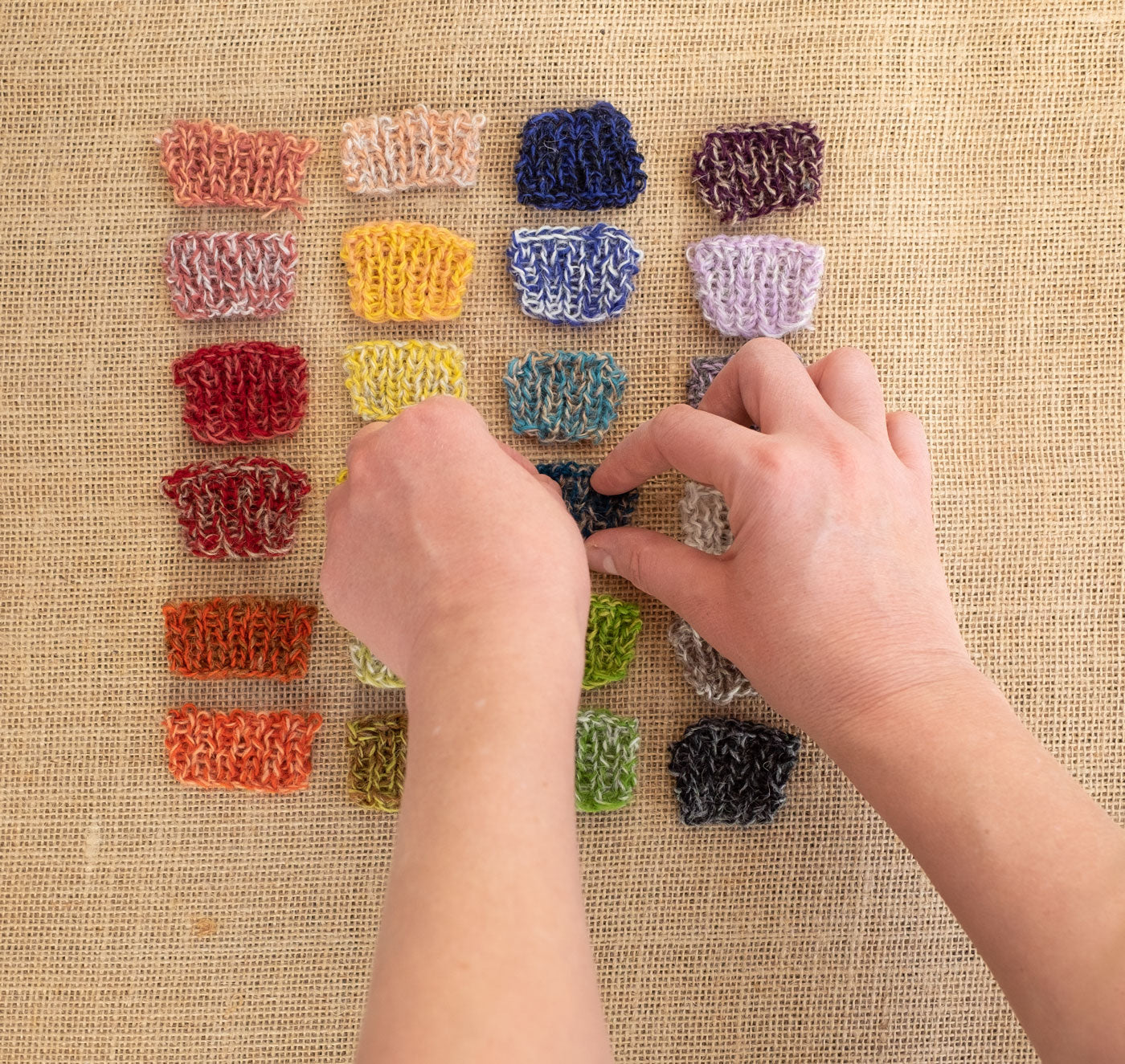 A grid of dozens of tiny swatches, testing many combinations of pairs of colors marled together. Two hands reach into the frame to straighten the swatches.