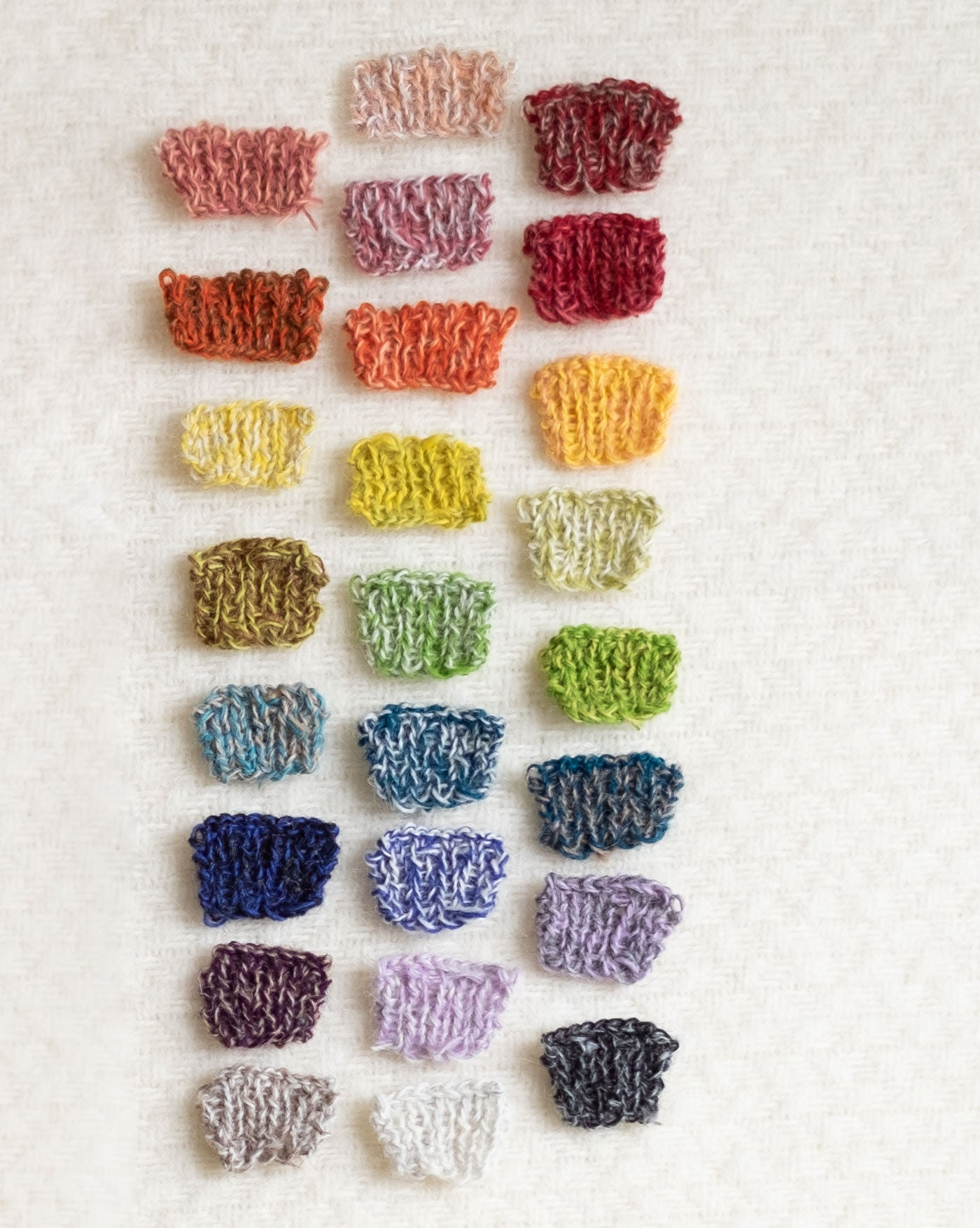 25 tiny knitting swatches in a rainbow of various combinations of two-color marls are laid out neatly on a soft, fuzzy, white woven wool background.