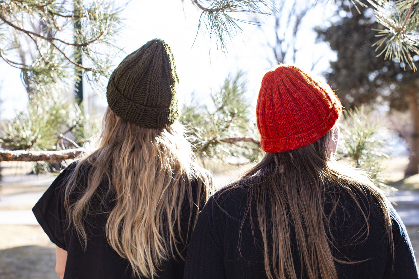 Two people in rib-knit beanies stand with their backs to the camera. Their long hair cascades out from under the backs of the hats as they look through the boughs of an evergreen tree and out toward a hiking adventure.