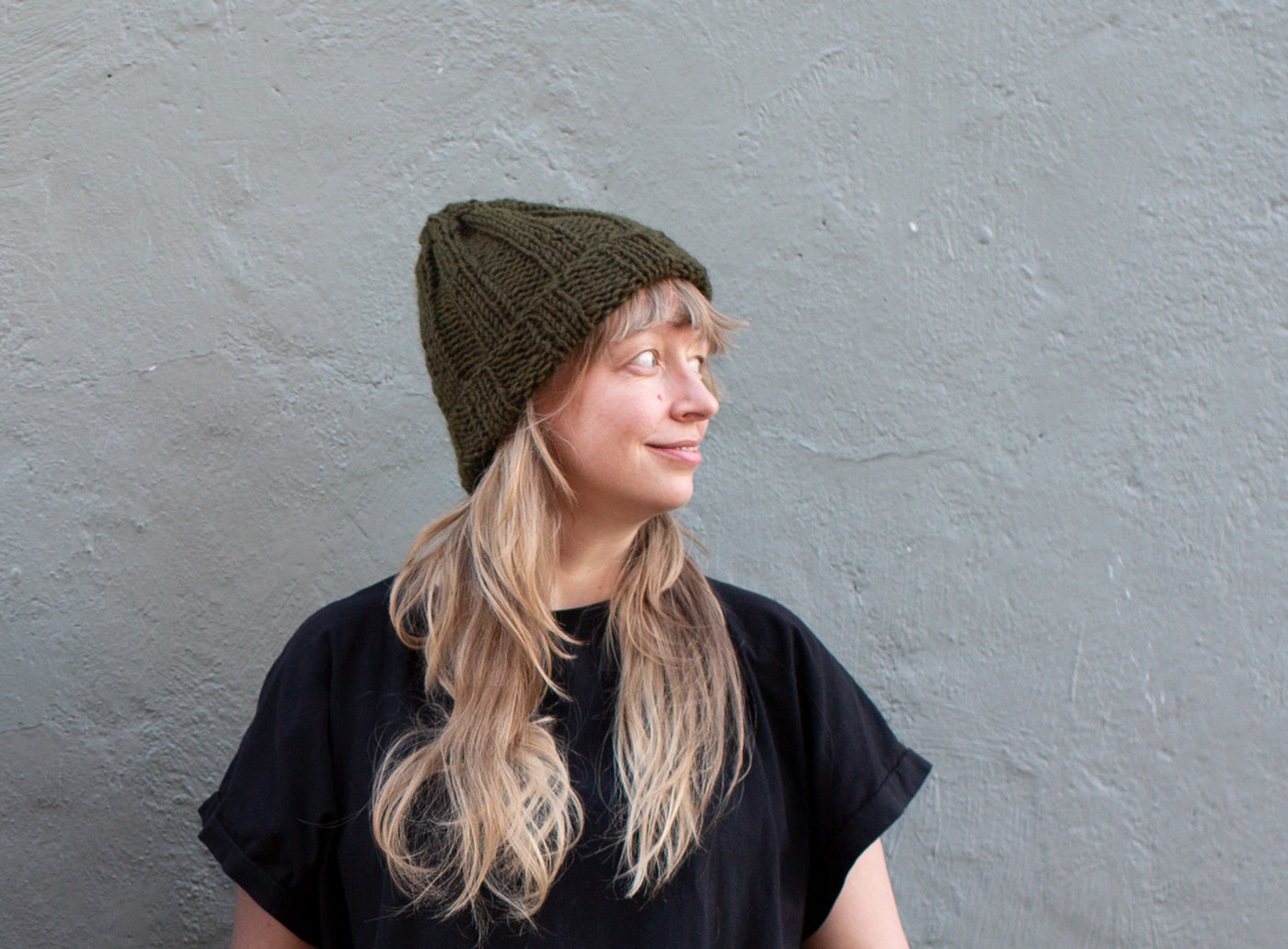 Amber stands in front of a grey wall, looking to the side, and wearing a cozy olive-hued, chunky knit beanie..