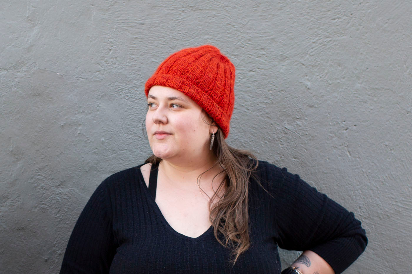 Marta stands in front of a grey wall, looking to the side, and wearing a vibrant, flame red-orange, fuzzy ribbed beanie.