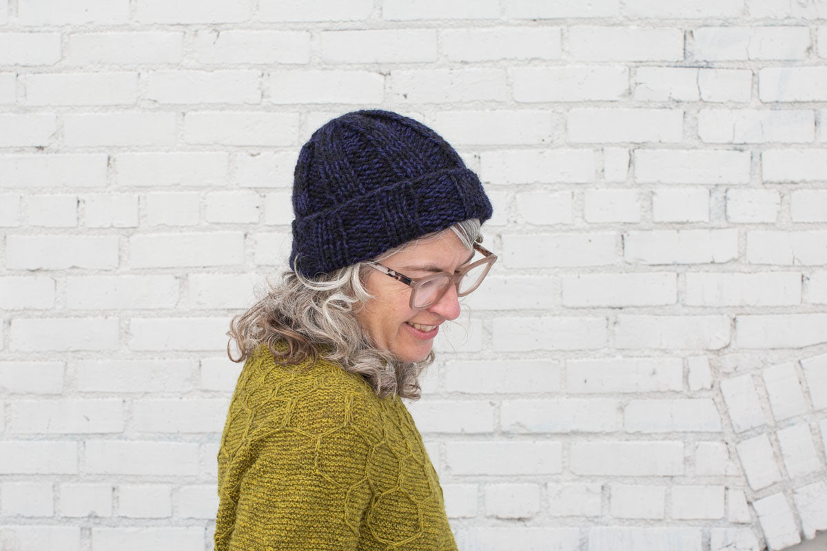 Jaime looks down, smiling. She wears a dark blue-purple and black marled ribbed beanie, and a sap-green handknit sweater.