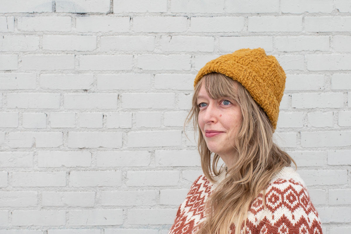 A close up of Amber wearing a handknit ribbed beanie—a bulky boucle yarn gives the hat a soft, sherpa-like texture. She wears a coppery brown and white colorwork yoked sweater.