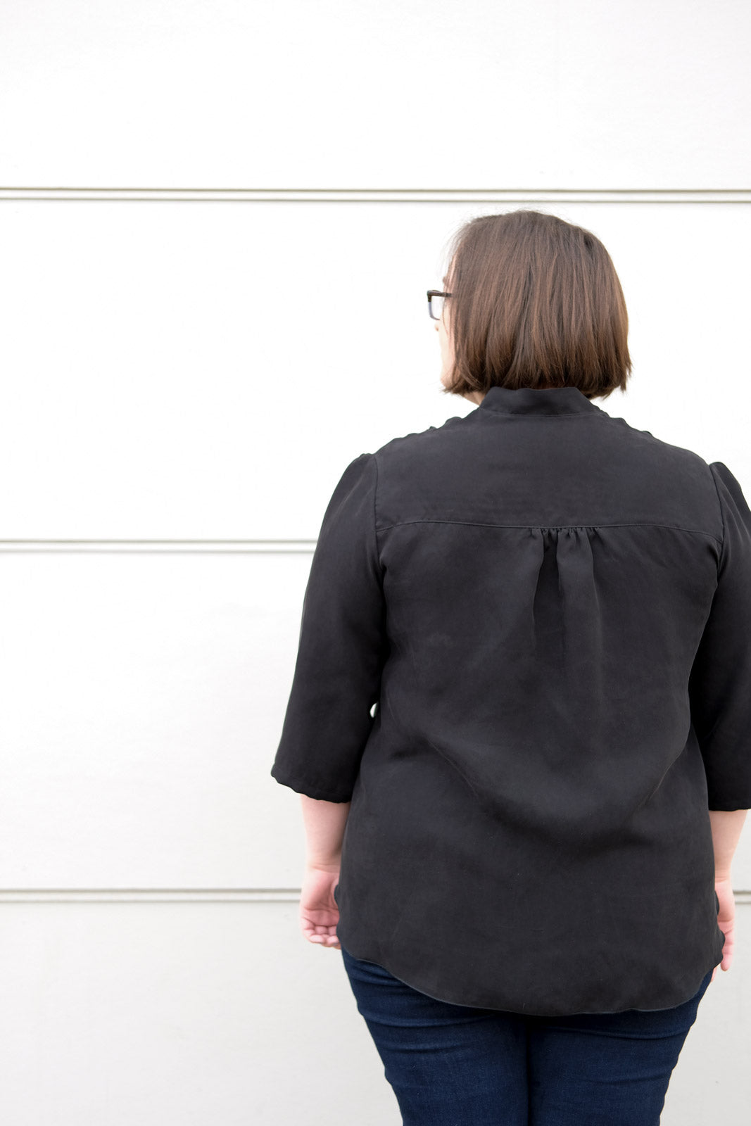 Close up of the back of a woman wearing a drapey black blouse, showing the gathered yoke.