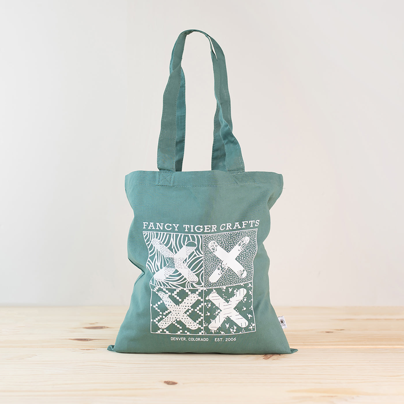 This is an image of a reusuable tote bag with the Fancy Tiger Crafts logo on the front of it sitting in front of a white wall and on a wood floor