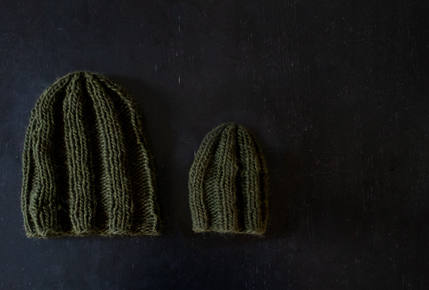 Two olive-hued, chunky knit hats lay on a dark wood background. The hat in the center is much smaller than the adult hat to the left of the photo. Adorably small, it is sized for a baby or toddler.