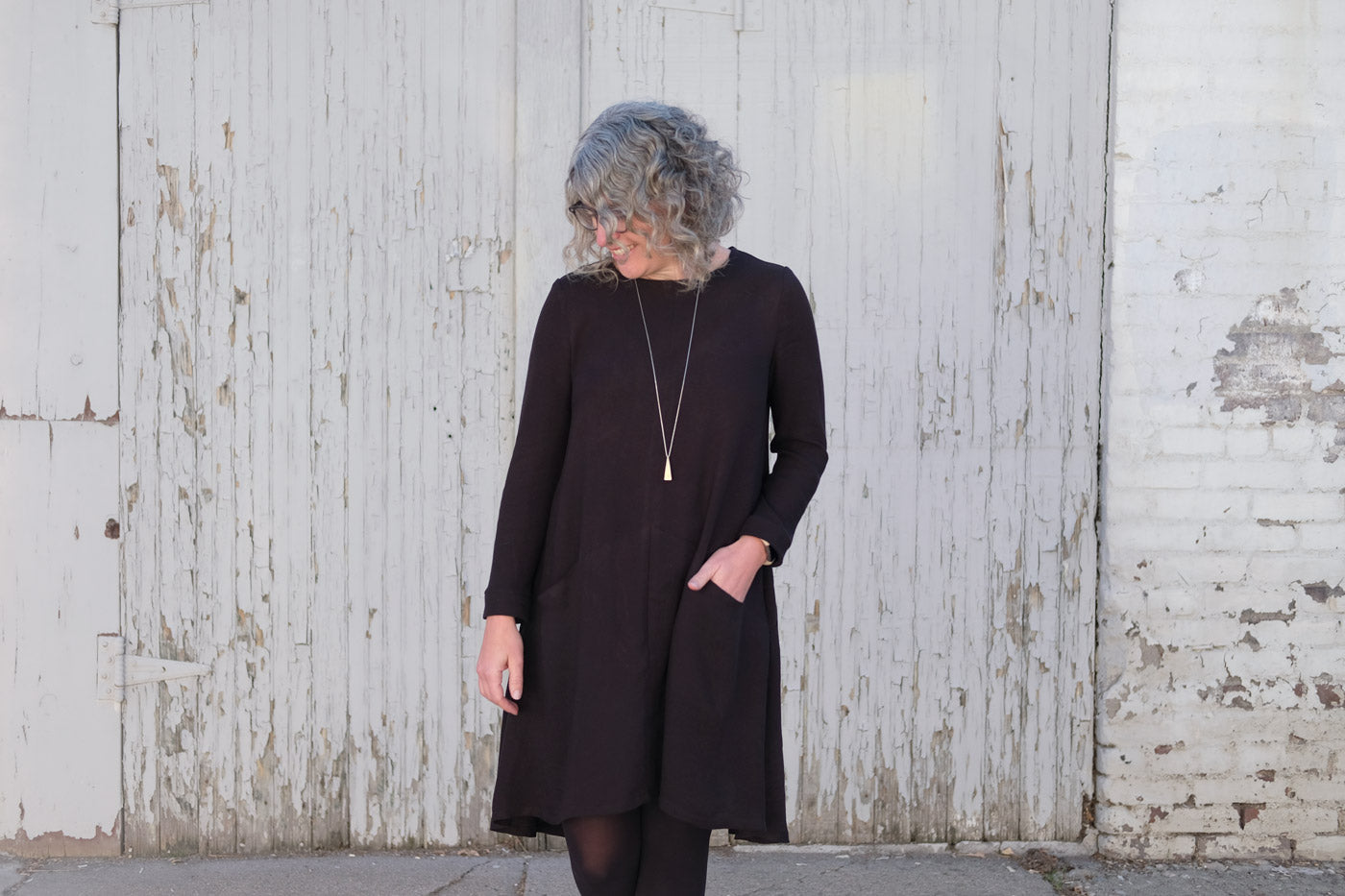 Jaime wearing her black Grainline Studio Farrow Dress and looking at the ground