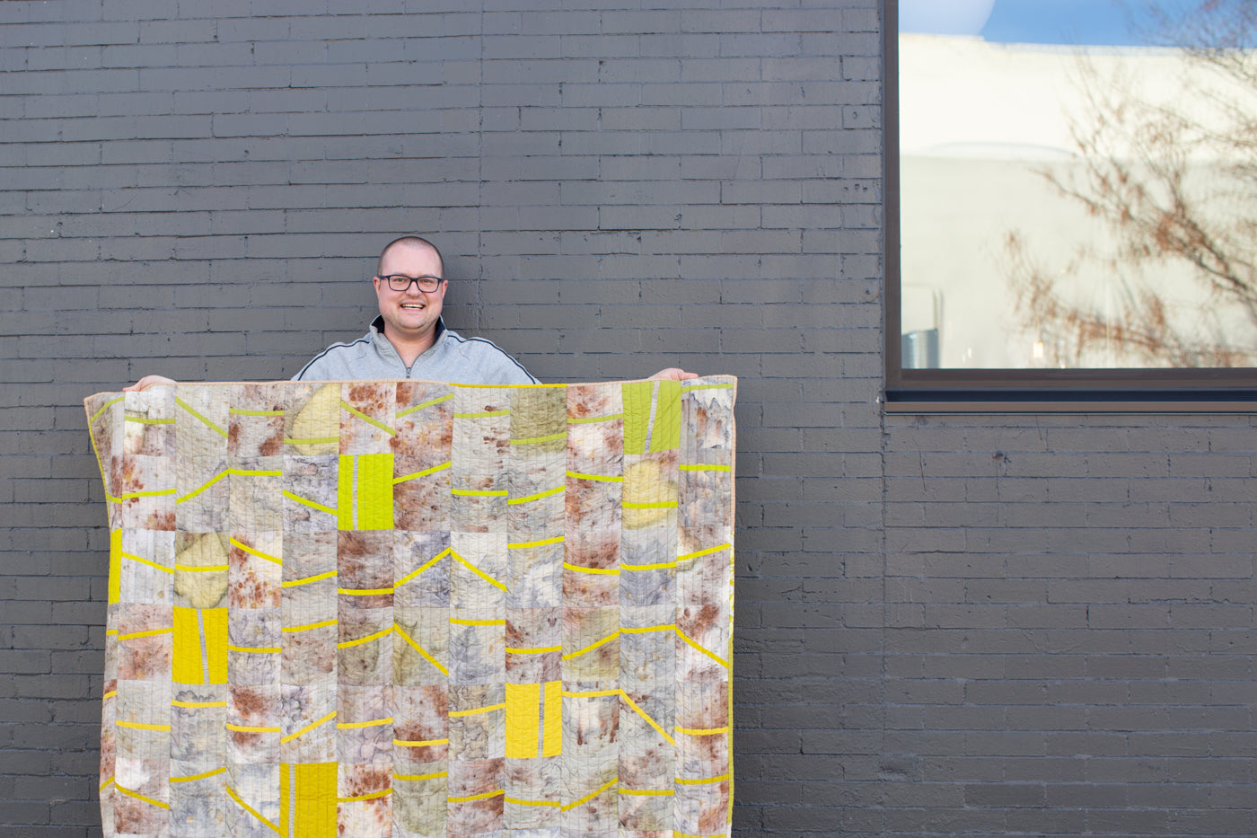 Man holding up quilt in front of a grey brick wall.  Man is wearing a light grey shirt, glasses and is holding up a quilt with brown, green soft color hues and blocks of bright yellow and green squares.