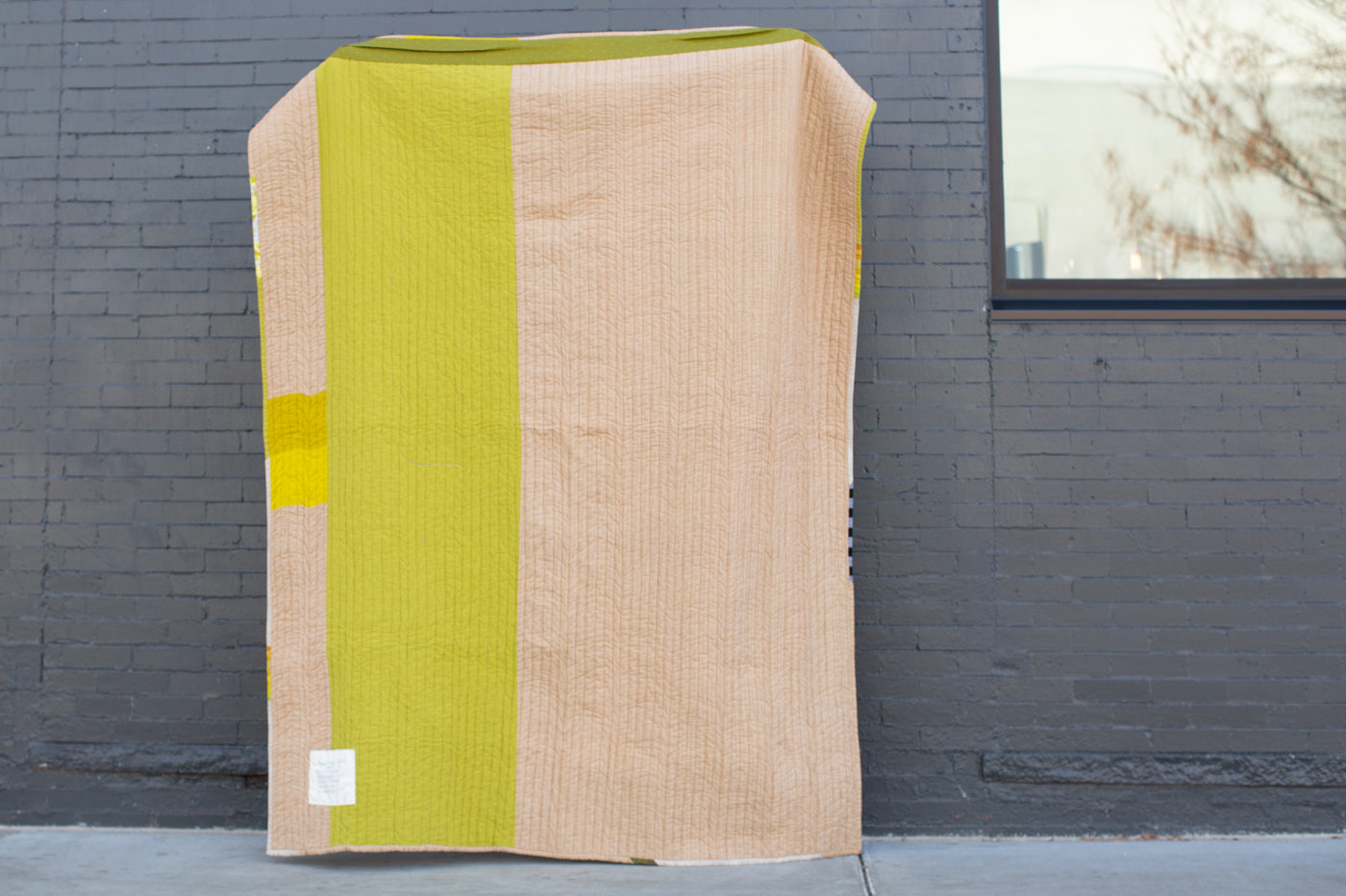 Quilt being held up against a darker grey brick wall.  The back of the quilt is striped with light brown, and a bright green panel.  With two small squares on the left side brown stripe that are yellow and medium green..