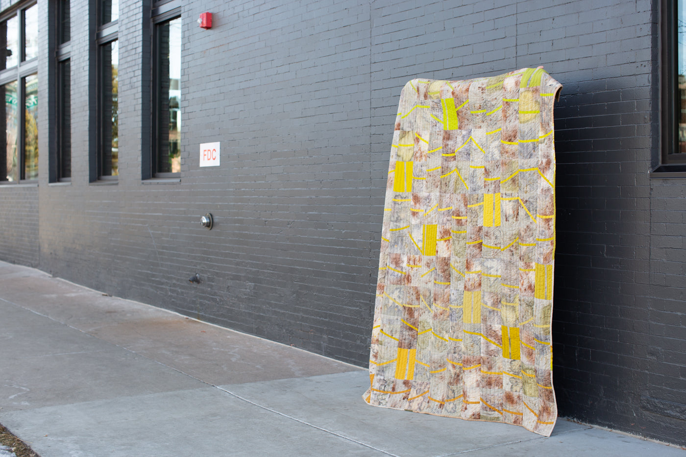Quilt being held up to show the front of the quilt on a city sidewalk against a dark grey building.  The quilt is multi colored with brown, green, yellow and red hues.