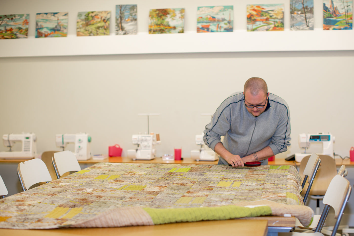 Bob with his quilt laying on a high top table, in the sewing classroom using a lint brush to remove any stray hair.