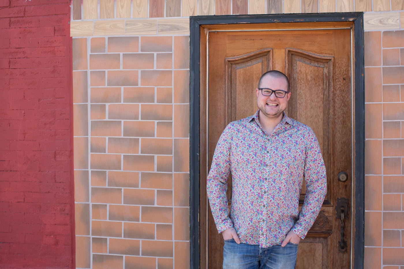 Bob wearing his long sleeved Fairfield floral shirt with his hands in his pockets, smiling at the camera.  Bob is standing in front of a wooden door of a brick building with accents of bright barn red brick.