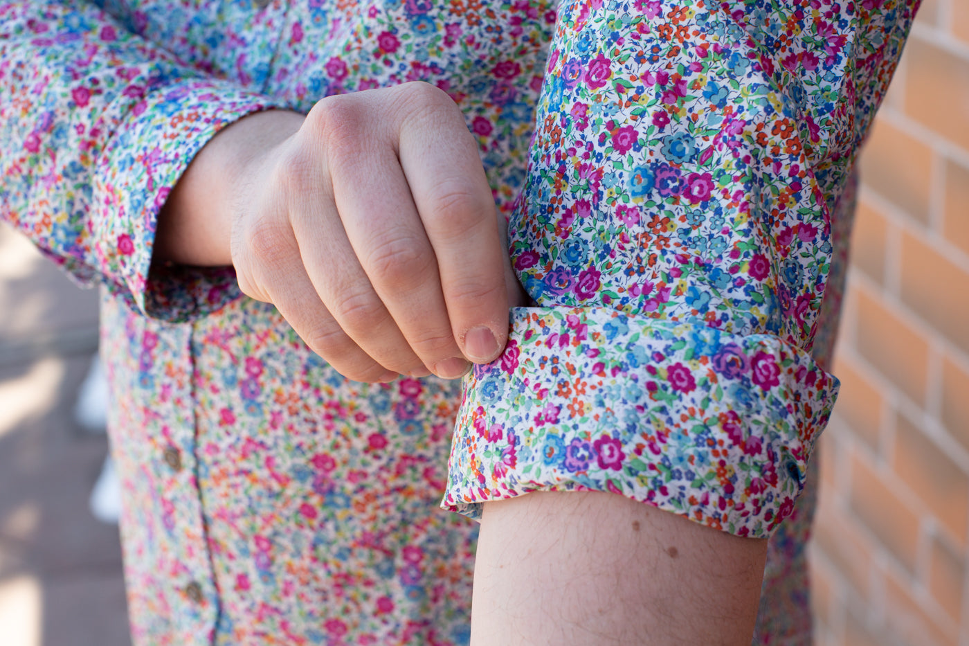 Up close detail photograph of a Bob rolling up his floral long sleeve making a cuff.
