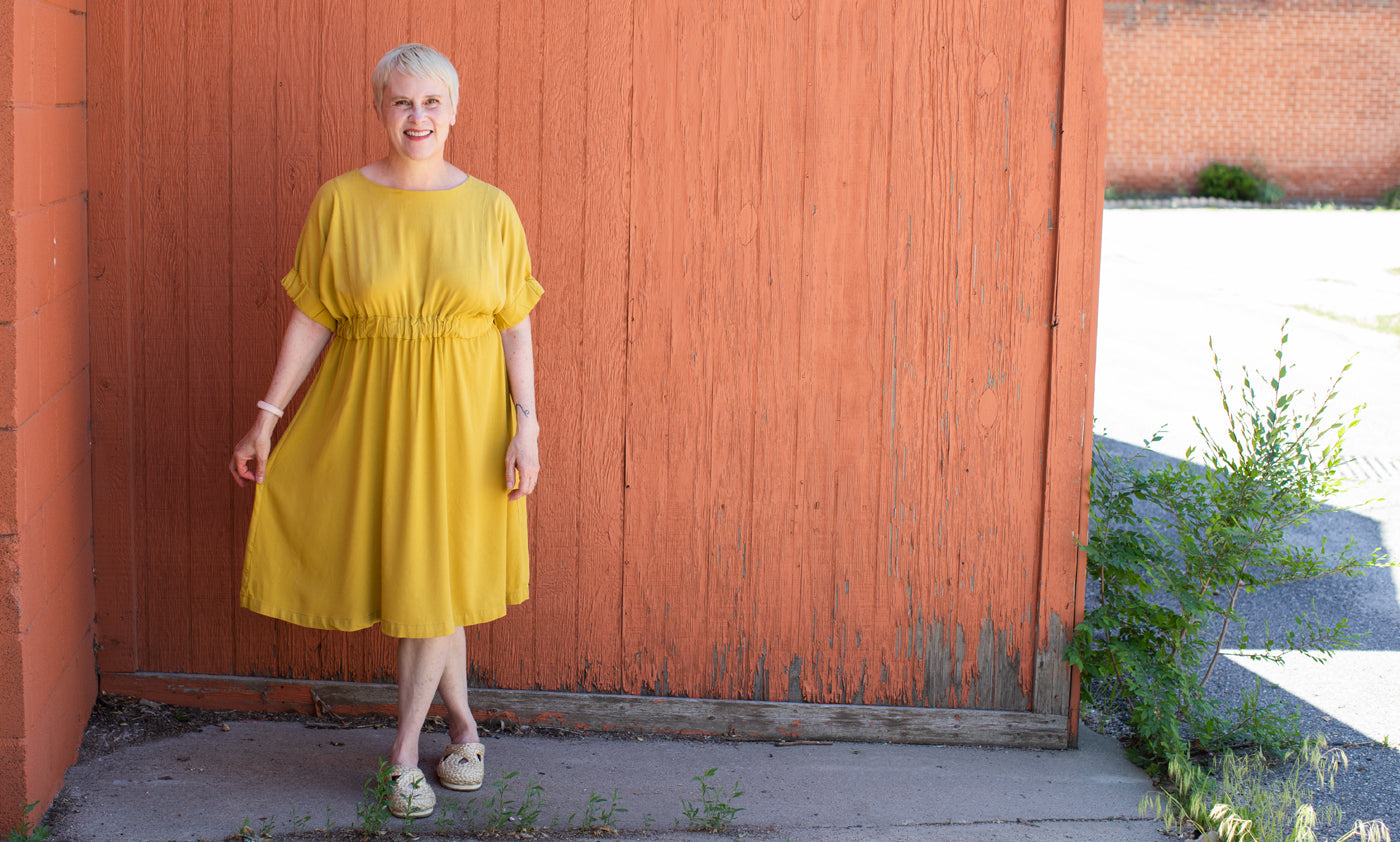 This is an image of a woman wearing a yellow dress standing in front of an orange wall.