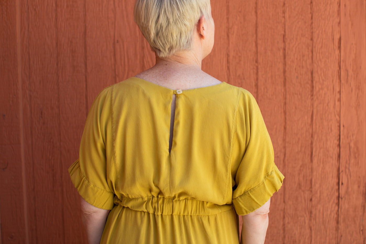 This is a photograph of the waist and back details of a woman wearing a yellow dress