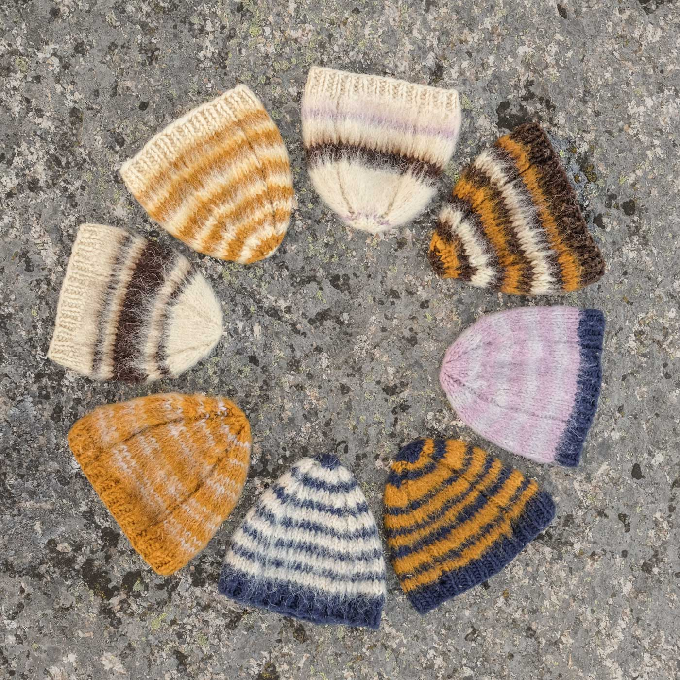 Seven Cobertor Caps laid down in a circle, each one is striped differently and they are a mix of colors.