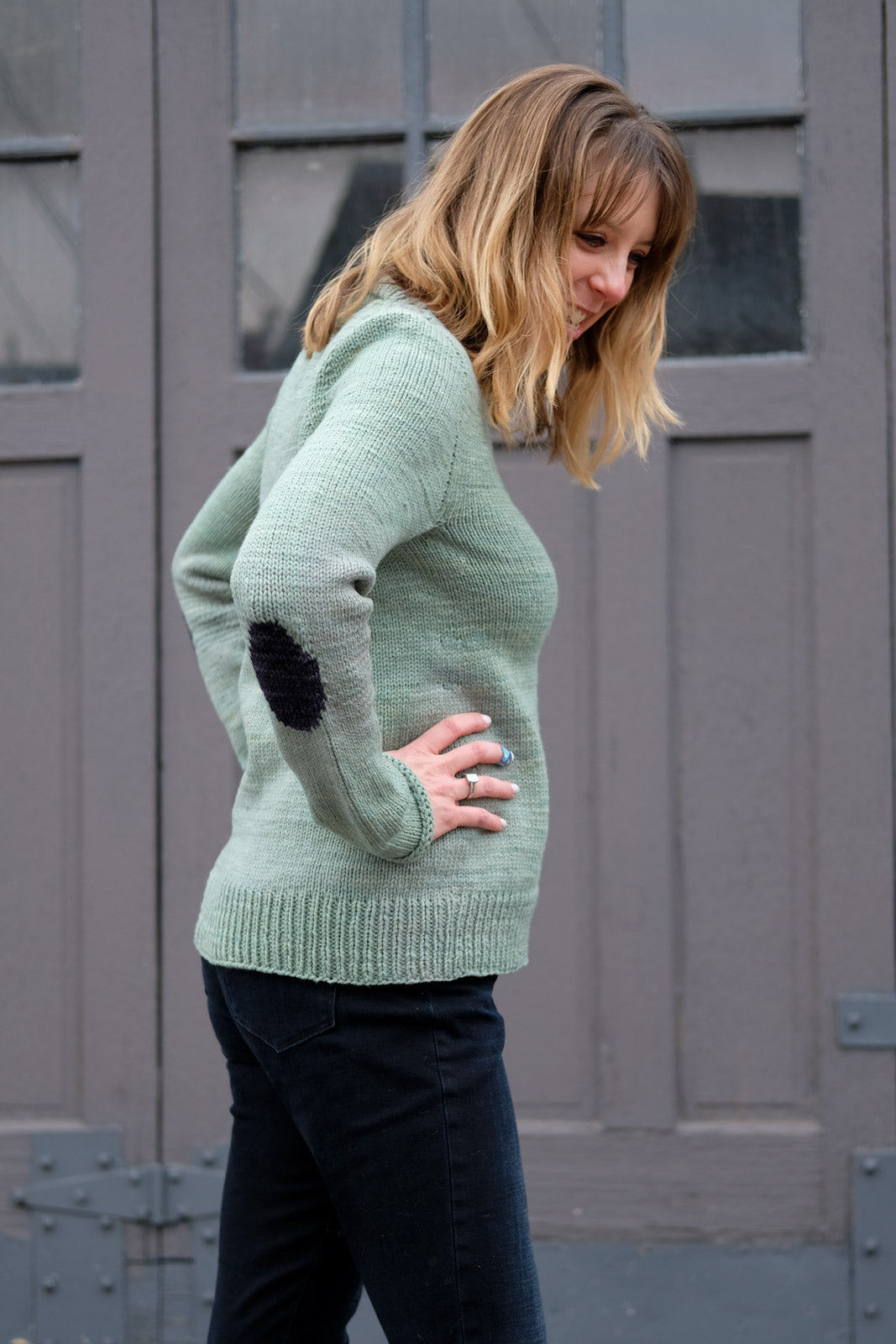 View of Lizz in her Molly Sweater- Hands on hips showing off her knit-in elbow patch