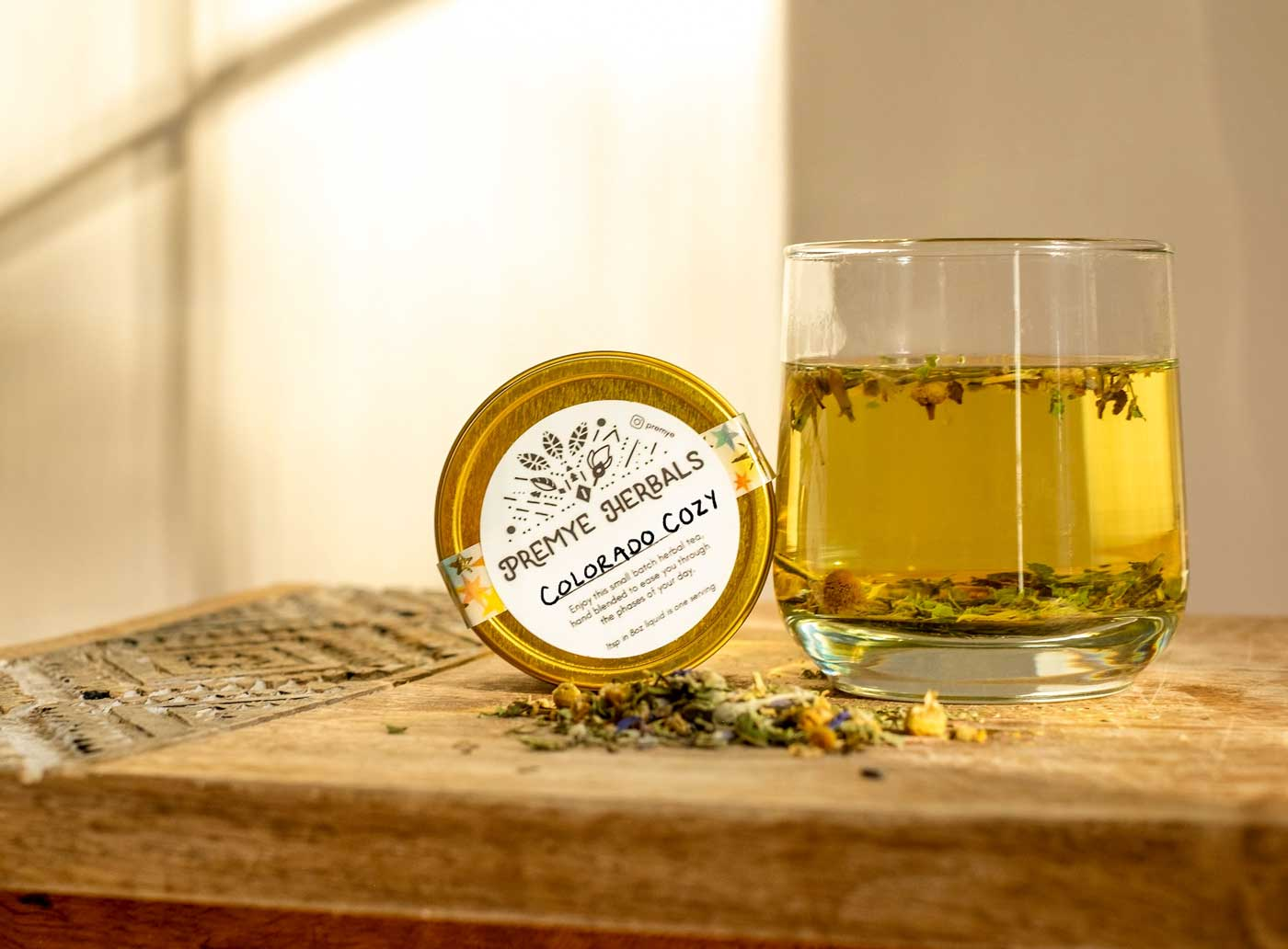 A tin of Colorado Cozy tea on its side with herbs scattered, and a glass with fresh herbal tea next to it.