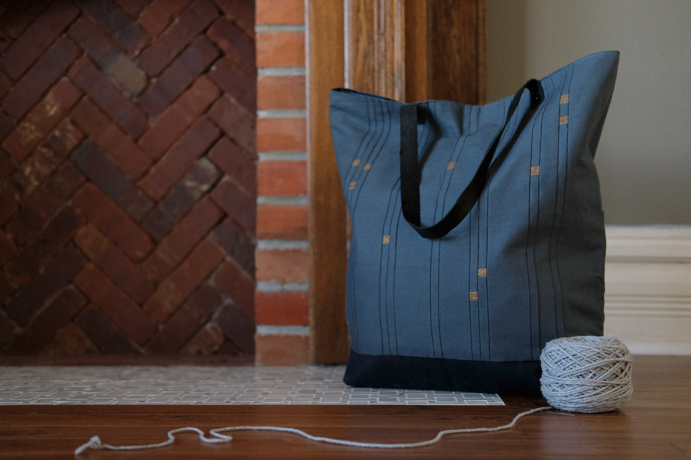 Blue Star Sign Tote sitting in front of a fireplace with a yarn ball next to it