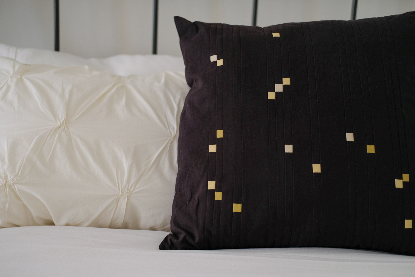 Constellations Book Orion quilted pillow sitting on a white bed