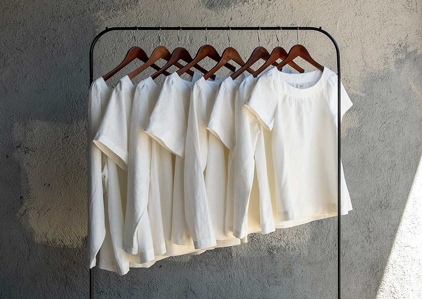 Eight solid white linen Cordyline tops in a range of sizes hanging on a rack.