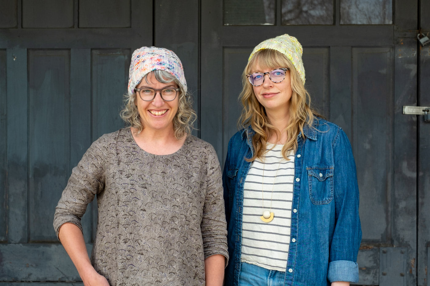 Jaime and Amber standing together, both wear handknits hats that are white with neon speckles.