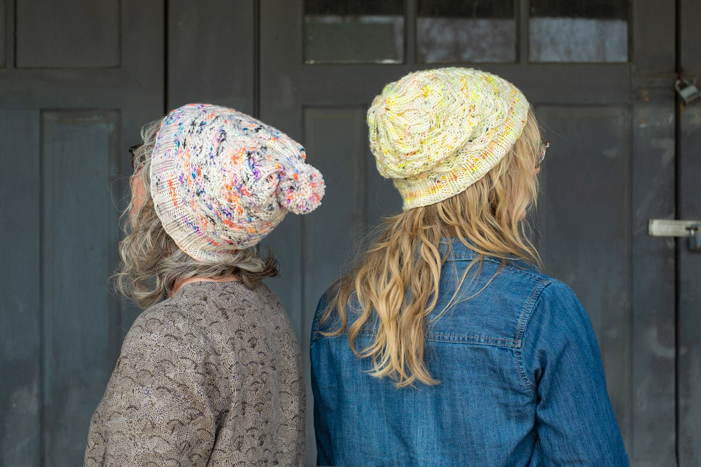 Jaime and Amber standing back to back, both wear handknits hats that are white with neon speckles, amber's is yellow speckles and Jaime's is coral, purple and blue speckles. The hats have a textured stitch.