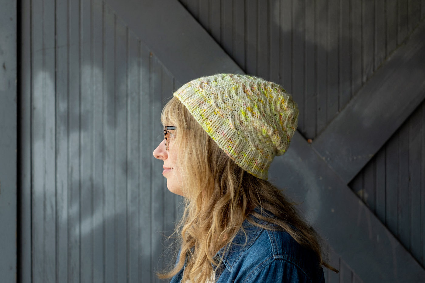 Side view closeup of Amber in her handknit hat, textured stitches in white yarn speckled with neon yellow, gold, and coral flecks here and there.