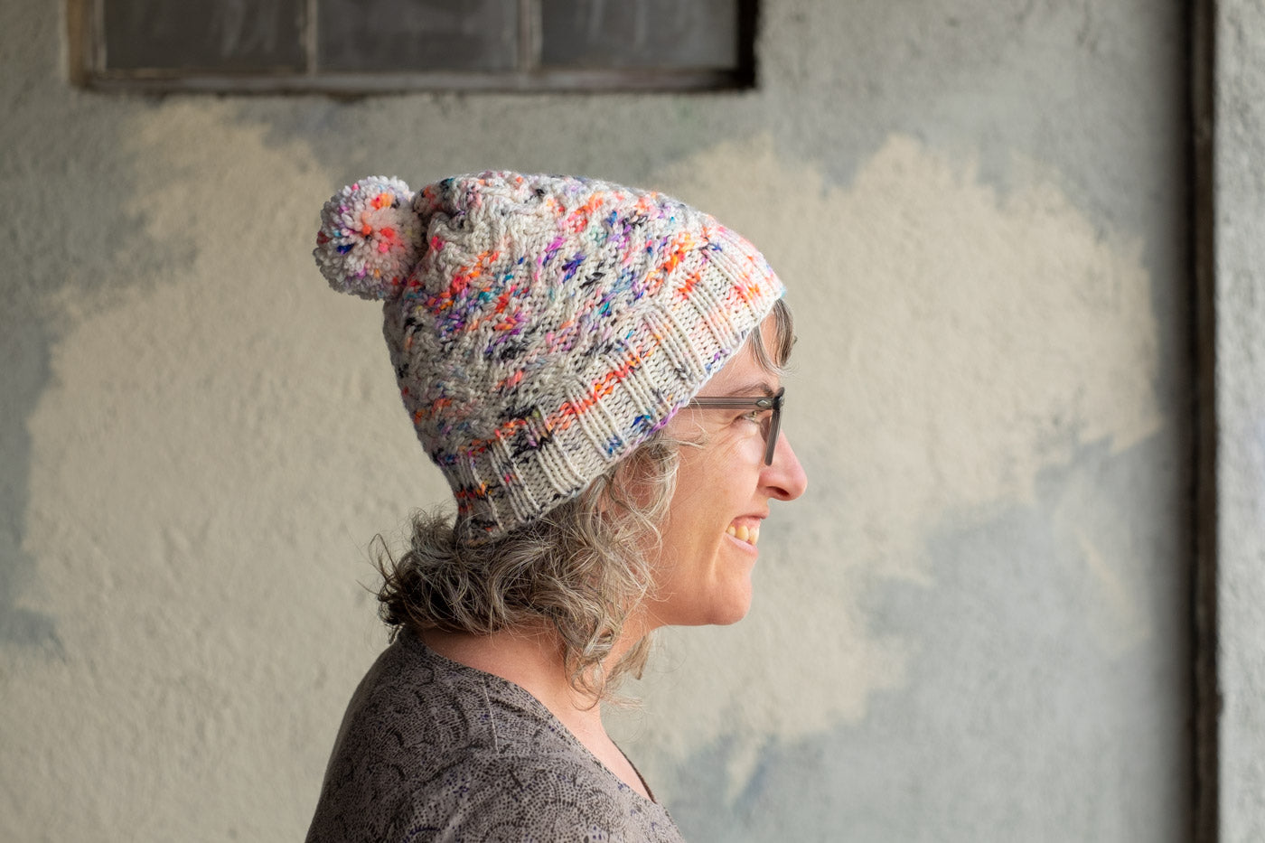 Side view closeup of Jaime in her handknit hat, textured stitches in white yarn speckled with coral, purple and blue. There is a pom-pom on top made from the same yarn.