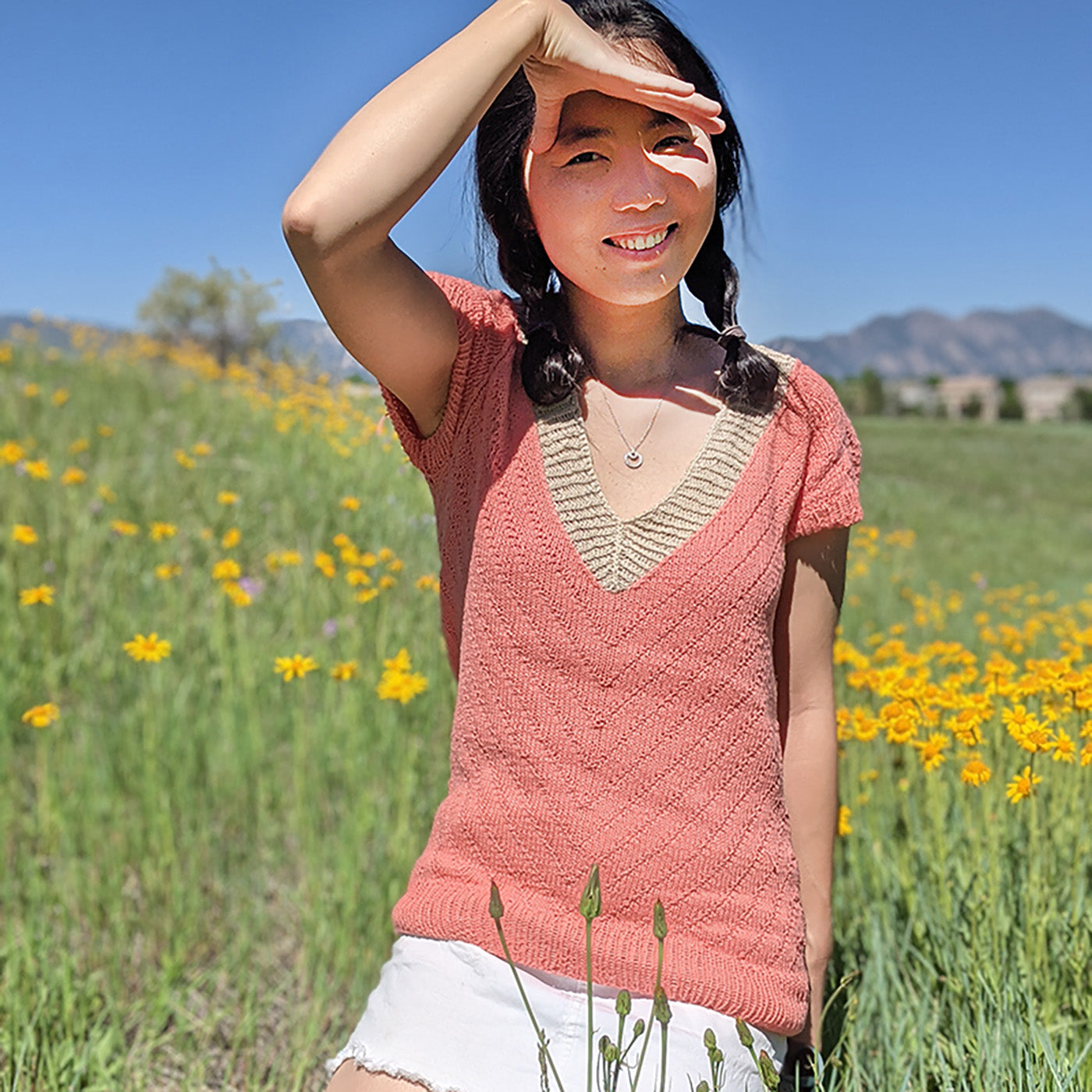 This is an image of a woman wearing a pink knitted sweater short sleeved shirt sitting in a field with yellow flowers