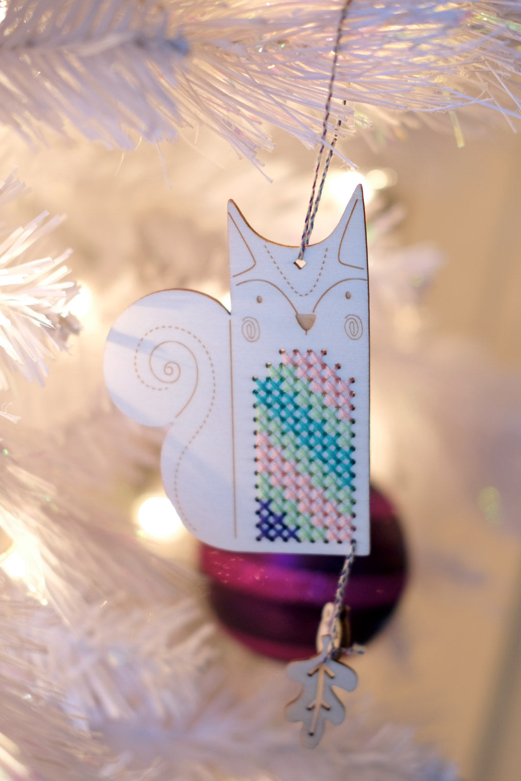 Stuart the Squirrel Crafty Like a Fox ornament hanging on a white tree