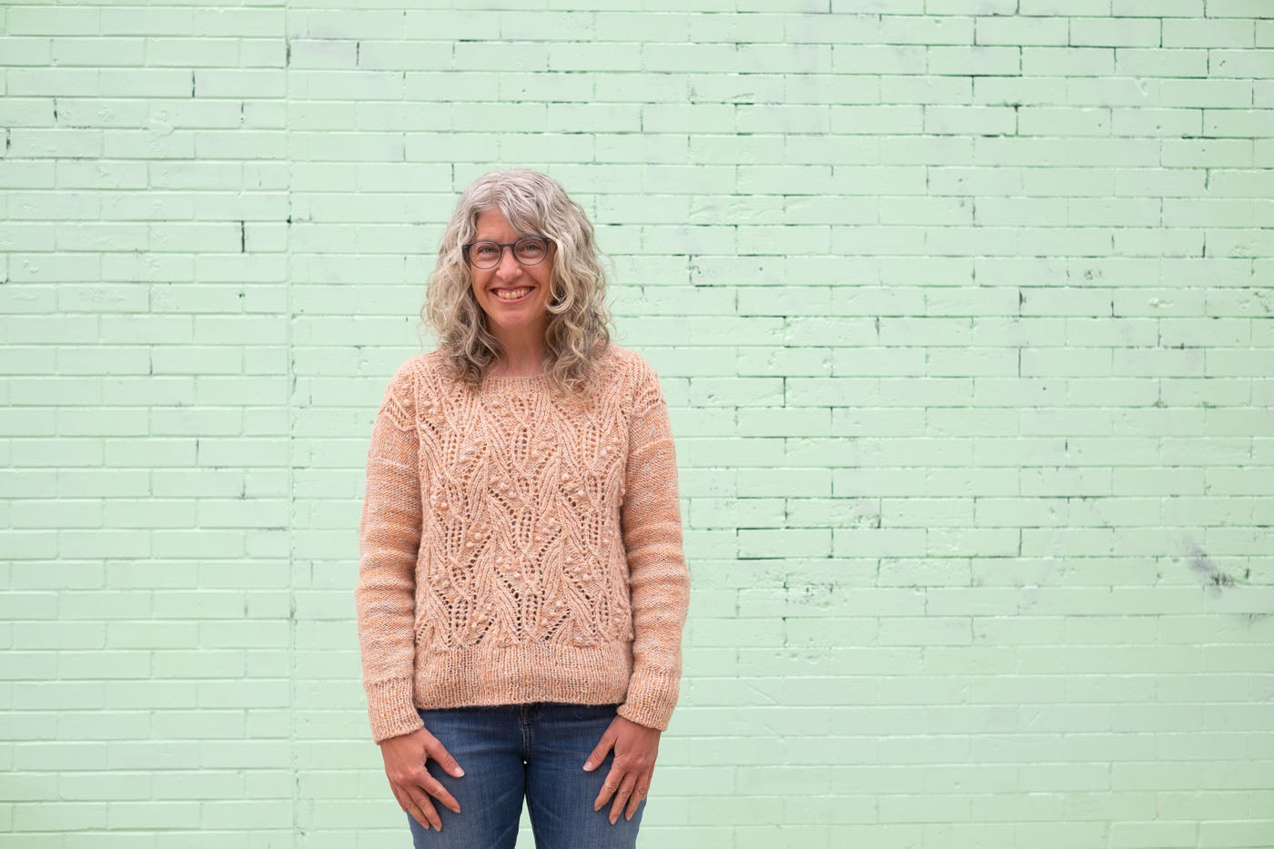 Jaime stands in front of a mint green painted brick wall, wearing her newly finished hand-knit Atlantica sweater. The textured sweater is the pale peachy color of spring blossoms, and Jaime smiles.